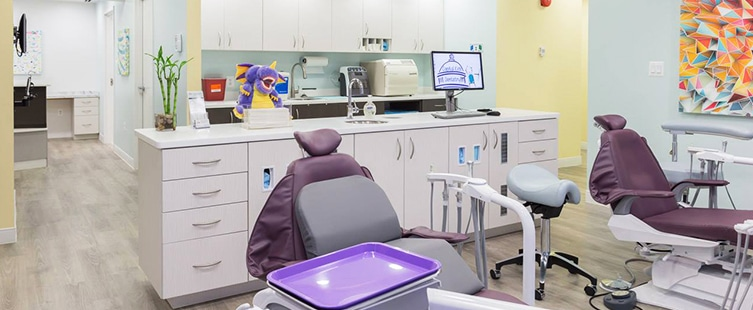 two purple dental examination chairs with white cabinets in the background