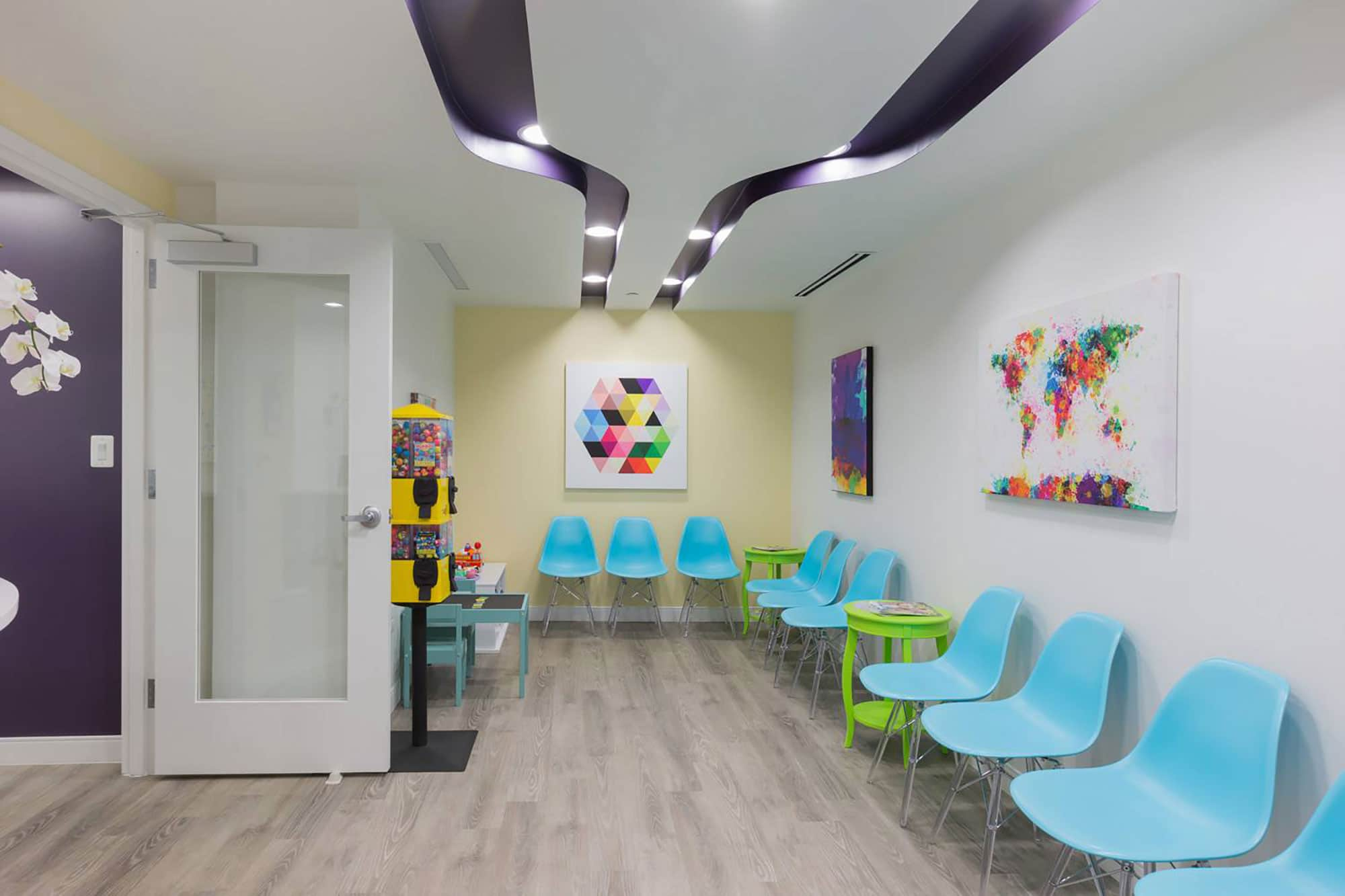 dental reception area with turquoise seats, kids play table and toy vending machines